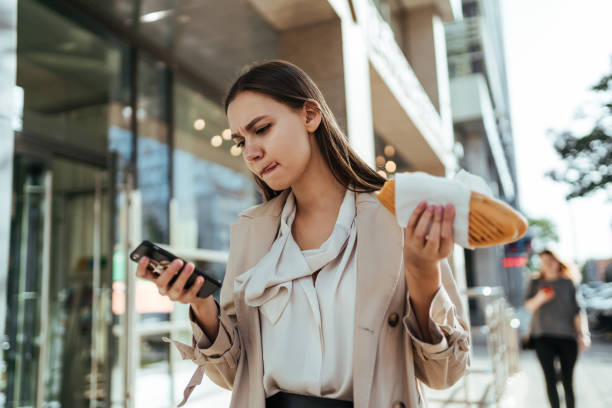 The busy businesswoman working online on a smartphone during a break The busy businesswoman working online on a smartphone during a break female sandwich stock pictures, royalty-free photos & images
