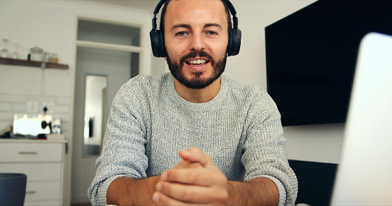 Portrait of a young man wearing headphones while using a laptop at home
