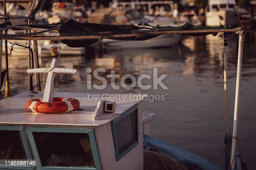 The cabin and mast of a small inshore fishing boat moored in a harbour. Port Anna, Sithonia, Greece.