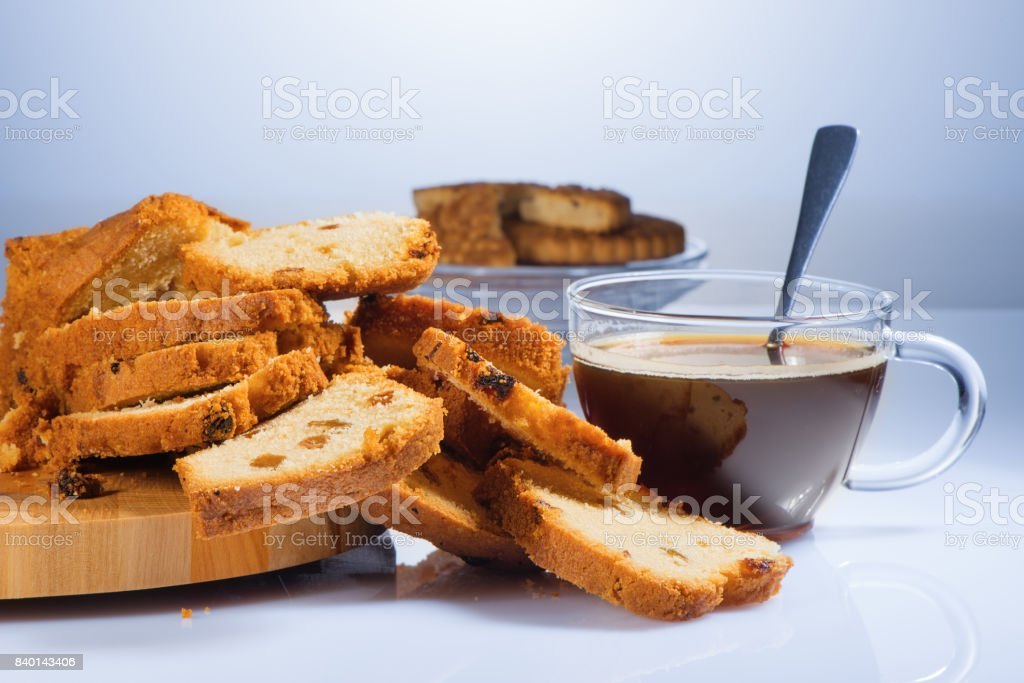 The cake cut on pieces with raisin on a beautiful chopping board and black coffee in a glass cup стоковое фото