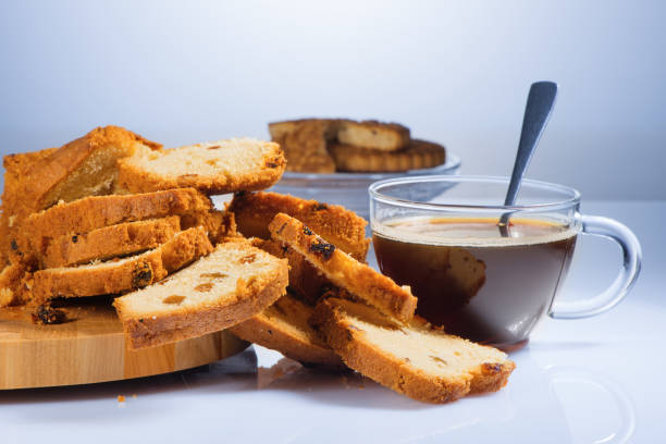 Cтоковое фото The cake cut on pieces with raisin on a beautiful chopping board and black coffee in a glass cup