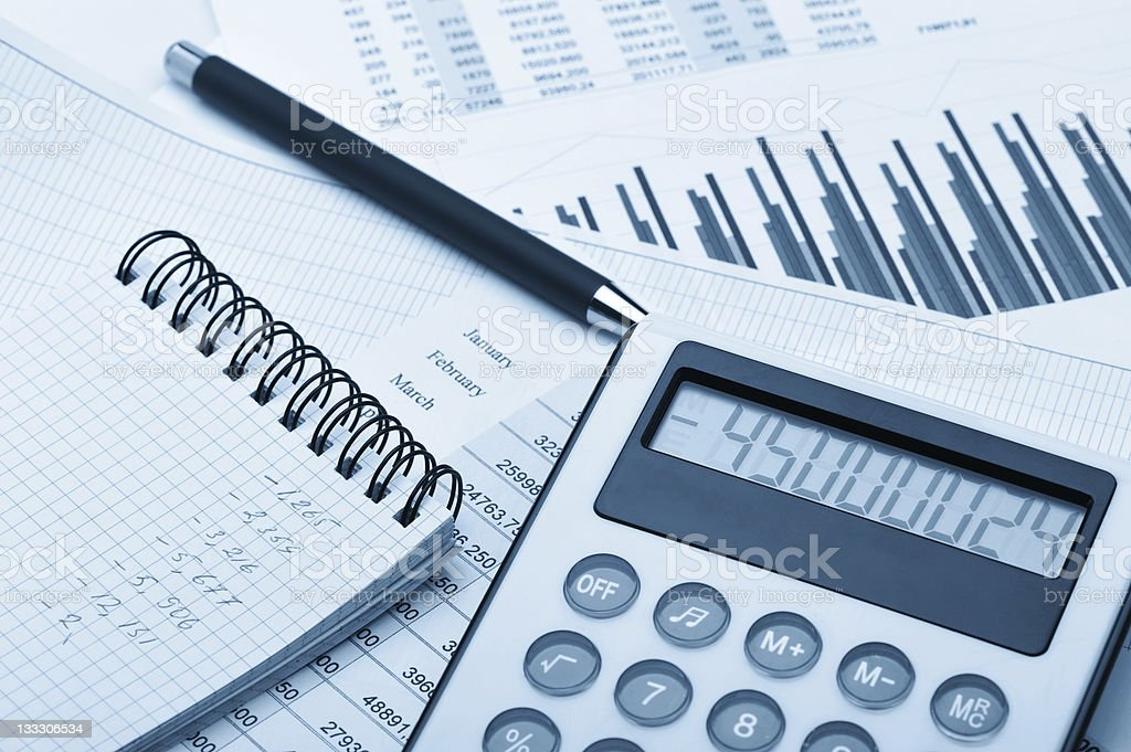 The calculator and financial report blue toned stock photo