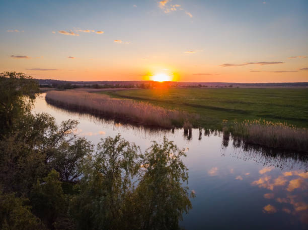 The calm surface of the river, orange sunset, green fields and meadows in a quiet warm summer evening stock photo