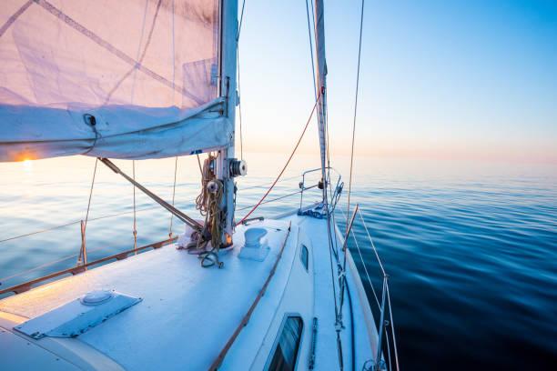 el agua tranquila. yate blanco aparejado navegando al atardecer. una vista desde la cubierta hasta la proa, el mástil y las velas. mar báltico, letonia - yacht fotografías e imágenes de stock