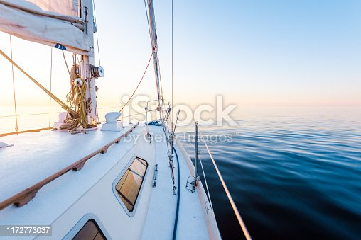 The calm water. White sloop rigged yacht sailing at sunset. A view from the deck to the bow, mast and the sails. Baltic Sea, Latvia