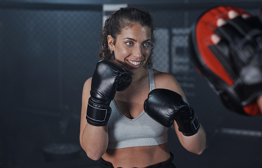 Shot of a young woman practicing with her coach at a boxing gym