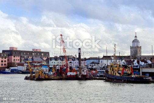 Portsmouth, Hampshire, England - November 1, 2012: A variety of boats in the Camber Docks, in Old Portsmouth, Hampshire. The Camber leads off Portsmouth Harbour and is the old original harbour. The old town is nearby and Portsmouth Cathedral can be seen to the right. (Background people. Overcast weather.)