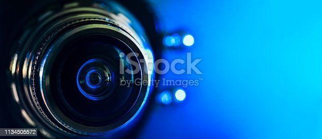 The camera lens and blue backlighting . Horizontal photography. Banner