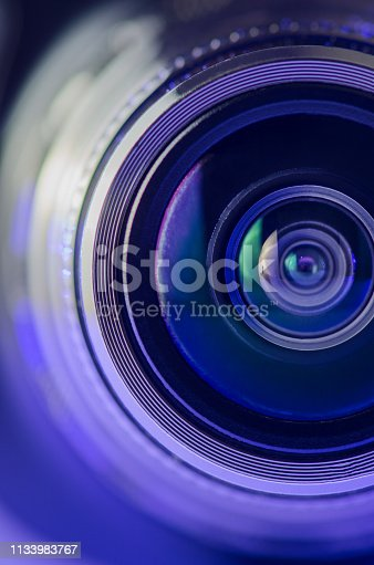 The camera lens and the beautiful light blue. Vertical photo