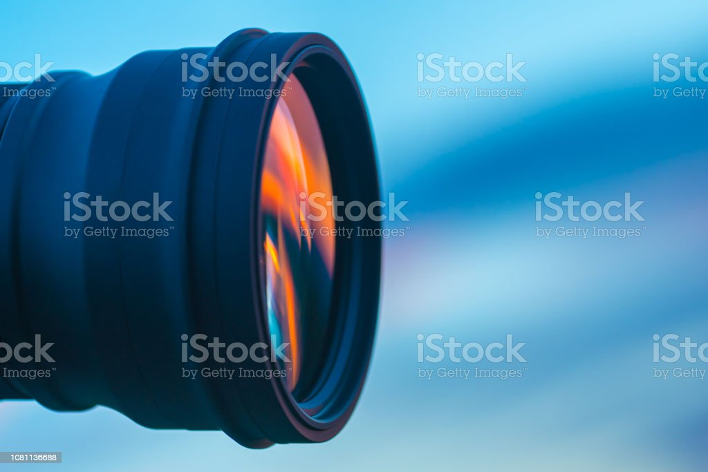 The camera lens on the background of a blue sky. close up view stock photo