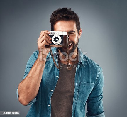 Studio shot of a handsome young man using a camera against a grey background