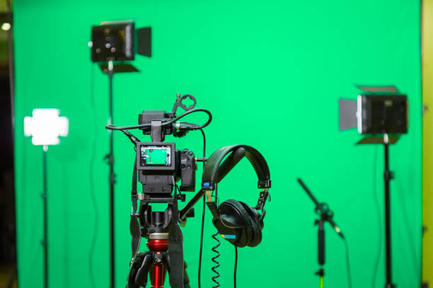 The camera on the tripod, led floodlight, headphones and a directional microphone on a green background. The chroma key. Green screen stock photo