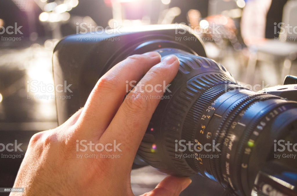 the cameraman is adjusting the focus and aperture settings of the camera stock photo
