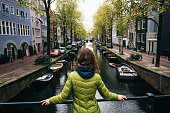 Young woman stands on the bridge and looks at the canal of Amsterdam, Netherlands