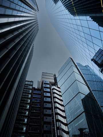 Low-key, geometric image, taken in the City of London. Image shows a scrap of grey, overcast sky overhead, almost crowded out by the enormous glass and steel sides of a group of London's skyscrapers, including the Lloyds Building. The image gives a sense of the power and scale of these organisations through the sense of scale it transmits.