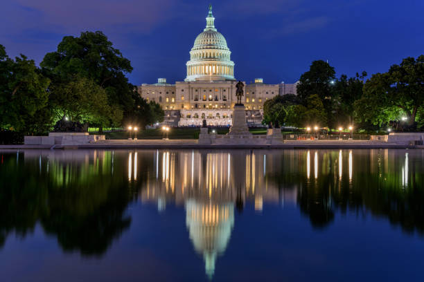 The Capitol and Reflecting Pool - A dusk view of west side of U.S. Capitol Building, with a small crowd gathering around a summer concert at front, reflected in Reflecting Pool, Washington, D.C., USA. stock photo