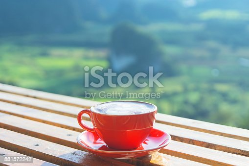 istock The cappuccino coffee in red cup put on the wooden table with beautiful mountain landscpe scenery and sun light in the morning. 881572242
