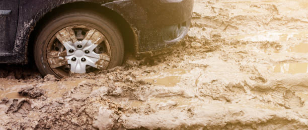The car got stuck on a dirt road in the mud. Wheel of a car stuck in the mud on the road. Car on a dirt road. stock photo