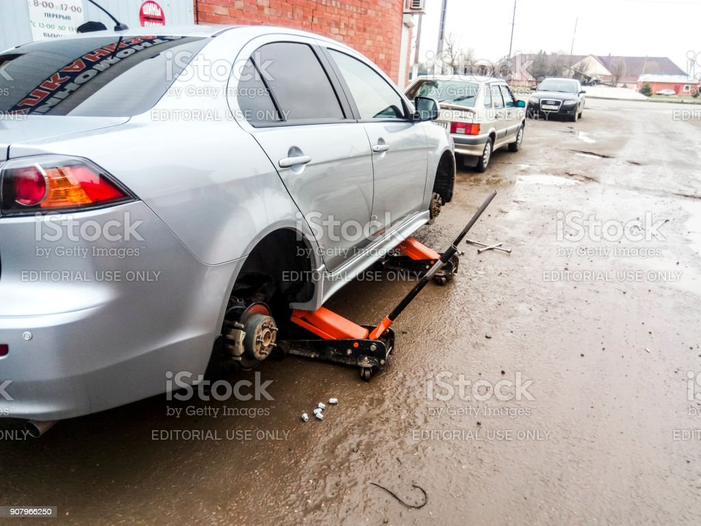 The car is at the tire shop. Under the jack the car in car-care...