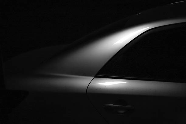 The car This photo was shooted in 2014 China, night dim light irradiation of the car, produce a glimmer of  light, with concise ornamental, black and white photos is more lines protruding, this photo for automobile advertising, or as the visual background. irradiation stock pictures, royalty-free photos & images
