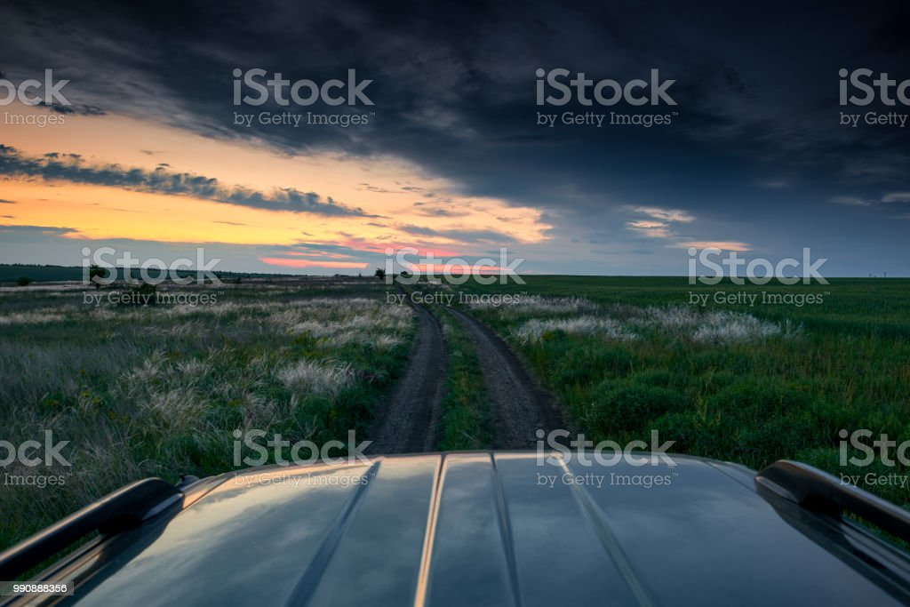 the car rides on a dirt road in the field, beautiful sunset with wild grass, sunlight and dark clouds stock photo