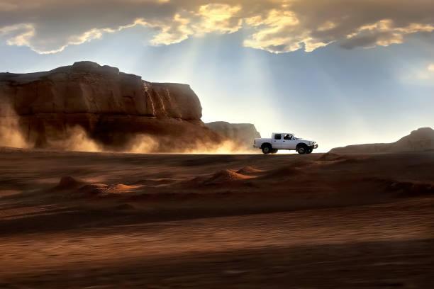 das auto fährt mit großer geschwindigkeit durch die wüste vor dem hintergrund der untergehenden sonne. schöne strahlen von licht und wolken. iran. kerman. dasht-e lut wüste. - rally stock-fotos und bilder