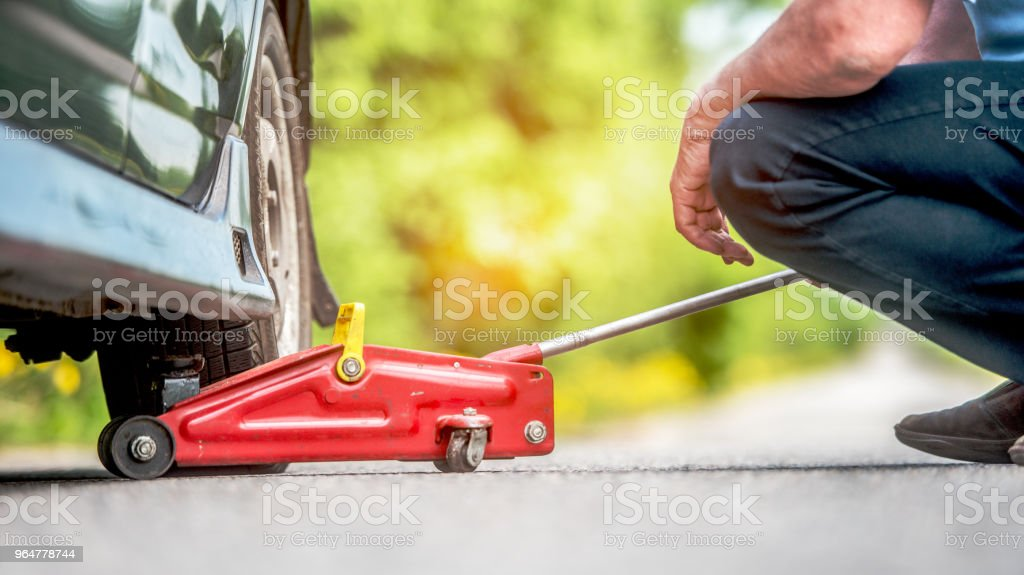 The car,  road, repair and a concept of accident - the driver of people lift in the way the car by means of a  track jack royalty-free stock photo