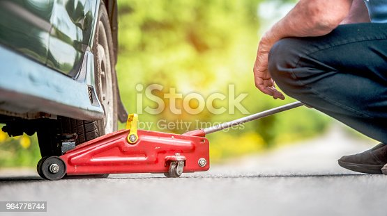 The Car Road Repair And A Concept Of Accident The Driver Of People Lift In The Way The Car By Means Of A Track Jack Stock Photo & More Pictures of Accidents and Disasters