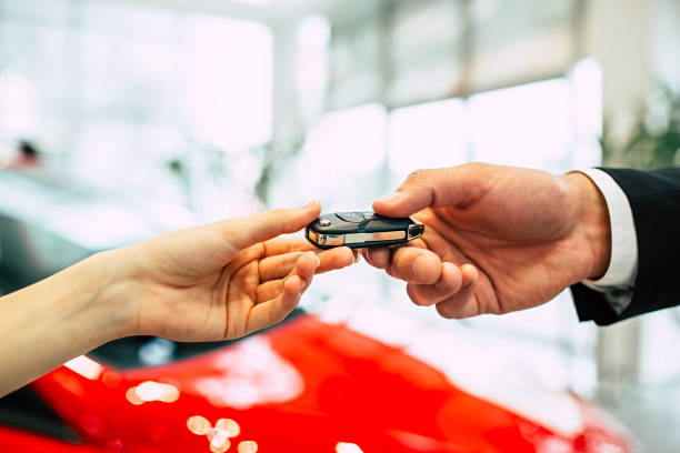 The car seller in the dealership passes the keys to the young woman. Handing of car keys. The car seller in the dealership passes the keys to the young woman. car key stock pictures, royalty-free photos & images