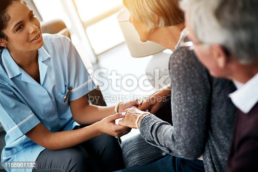 Shot of a young nurse holding hands with a senior woman while sitting next to her husband