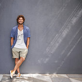 Full-length shot of a handsome young man leaning against a gray wall