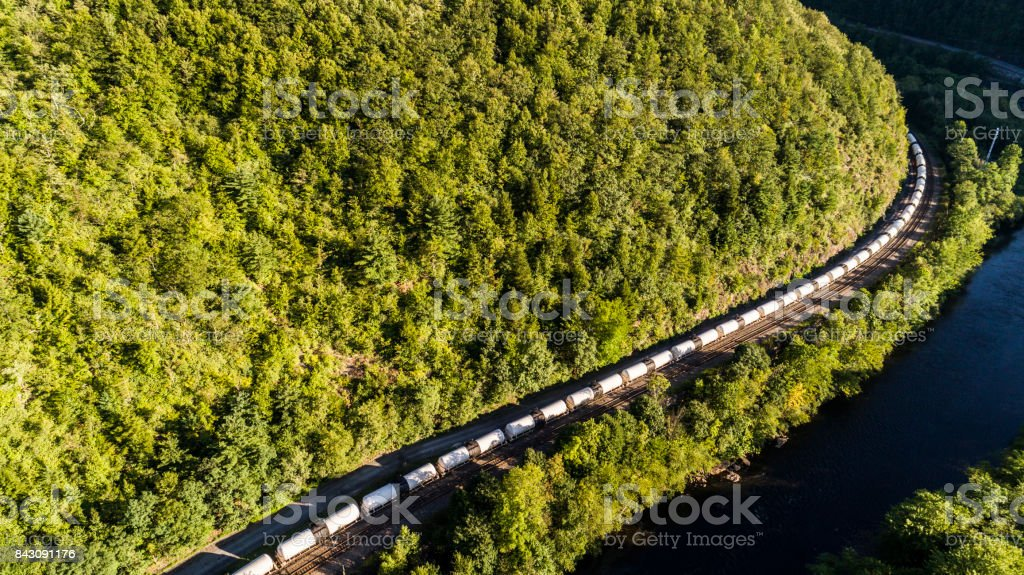 The cargo train on the railroad in Appalachian mountain along the Lehigh River, near by Jim Thorpe, Pennsylvania, USA. Aerial footage. stock photo