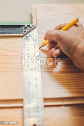 The carpenter marks the smooth cutting line on the board with the help of a construction square and a pencil
