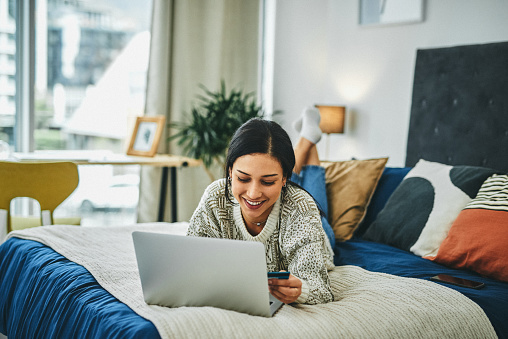 Shot of a young woman using a laptop and credit card on the bed at home