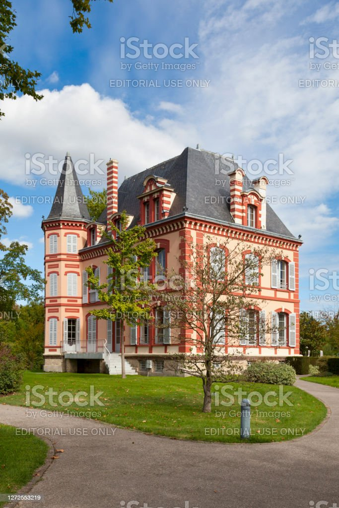 The Castelrose in L'Isle-Adam L'Isle-Adam, France - September 09 2020: The Castelrose is an old bourgeois residence which takes its name from the pink plaster of its facades. Built between 1875 and 1885, it served as a pension for war widows before World War II. The villa was then occupied by the German Kommandantur before becoming a pension after the war. It is today an annex of the town hall of L'Isle Adam. Architecture Stock Photo