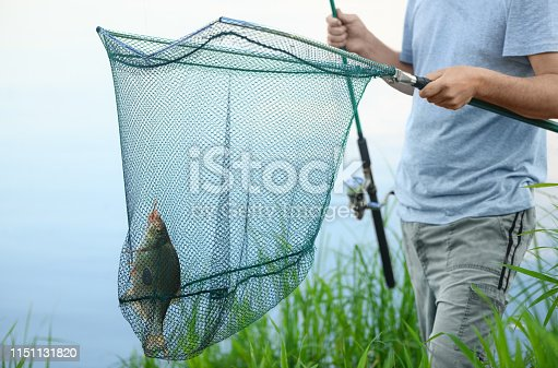 1030273092 istock photo The caught bream (Abramis brama) is in a landing net on a background of a water. The fisherman is standing on a riverbank and holding one fish and fishing rod in his hands in rural. 1151131820
