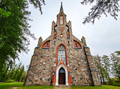 Cesvaine, Latvia - 07.23.2019: The Cesvaine Lutheran Church, a building of colored stones with a clock, against a blue sky, surrounded by green trees.