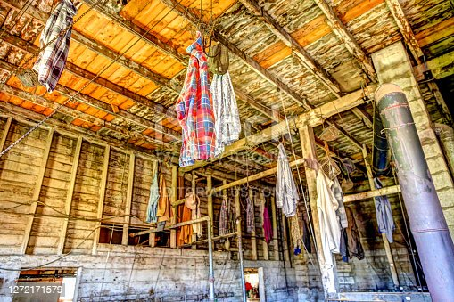 East Coulee, Alberta, Canada - July 3, 2020: Miners clothing hanging from the ceiling of the change room of the former Atlas Coal Mine in East Coulee Alberta. It is now a museum open for tours and has a rich history of coal mining in the region.