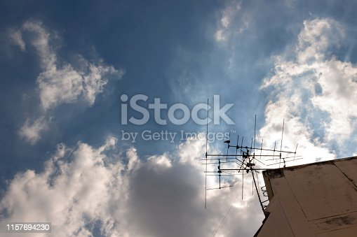 The chaos of cables and wires on electricity pole with blue sky and cloud.