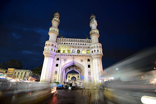 The Charminar after sunset Hyderabad, India – August 11, 2012: During the holy month of Ramadan, Muslims gather after sunset to eat, drink and shop in the busy bazaar around the Charminar in the hart of the old city. char minar stock pictures, royalty-free photos & images
