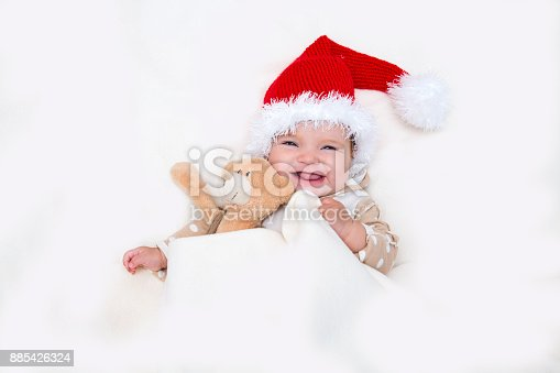 The cheerful Christmas baby to a Santa hat and Teddie's bear