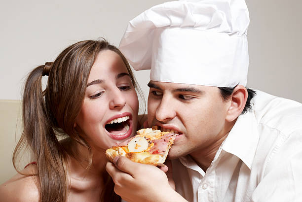 The cheerful couple eating a pizza stock photo