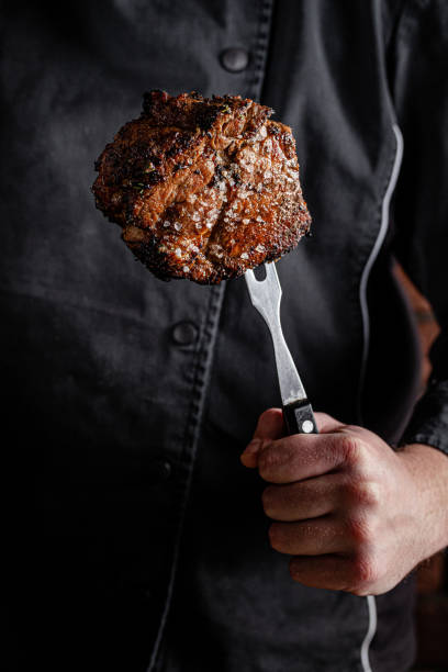 The chef cook is holding a beef steak in his hands on a fork. background image, copy space text