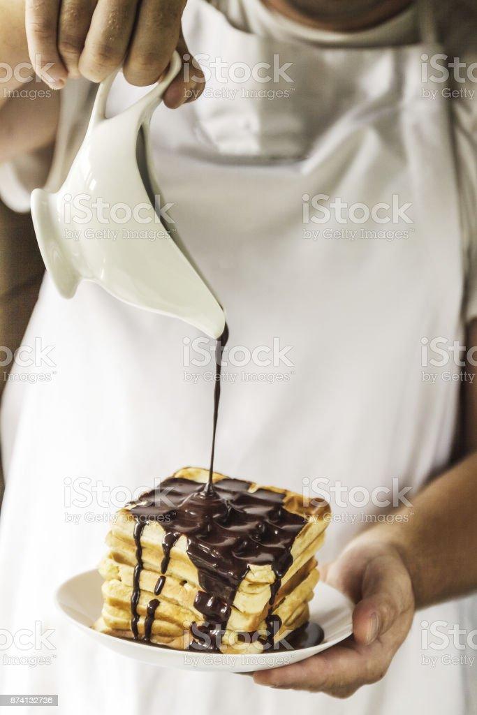 Le chef dans ses mains est titulaire d'une plaque avec des gaufres belges et leur verse avec sirop au chocolat - Photo