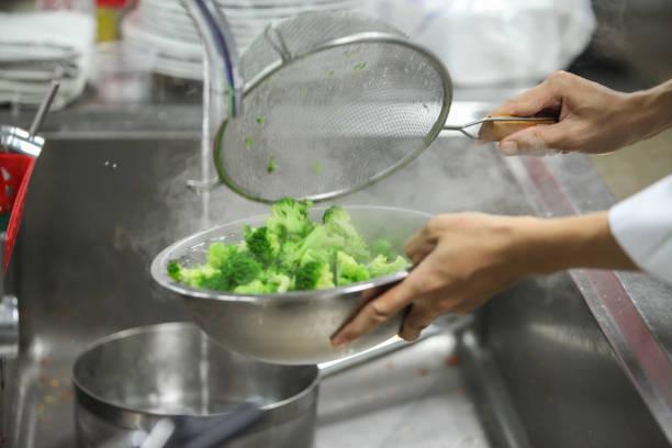 Der Küchenchef klopft Broccoli im kalten Wasser in der Küche an. – Foto