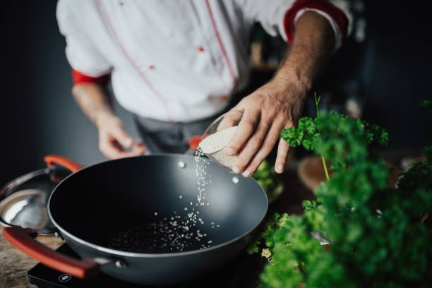 The chef is pouring sesame into hot pan stock photo