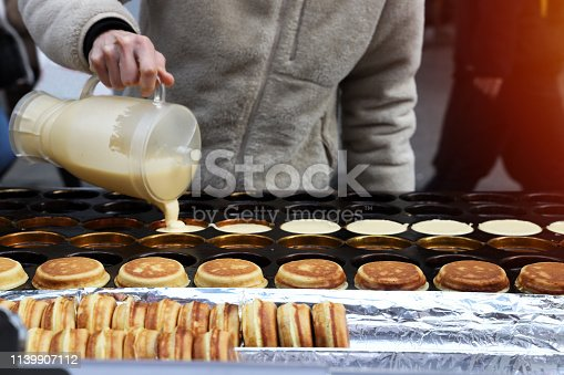 The chef is pouring the dough onto the stove with a hole for making pancakes. With the finished pancakes ready to be served on the front of the oven Pancakes are street food in Seoul, South Korea.