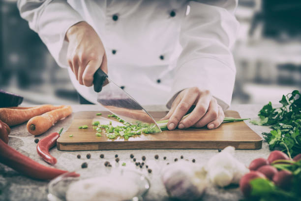 The chef slicing vegetables. chef cooking food kitchen restaurant cutting cook hands hotel man male knife preparation fresh preparing concept - stock image preparing food stock pictures, royalty-free photos & images