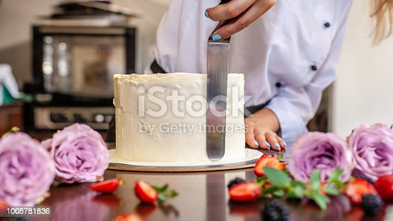 istock The chef's confectioner cooks a cake and decorates it with fresh flowers. background image. 1005781836