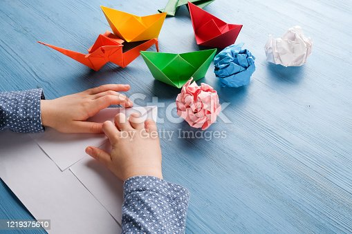 The child at the table makes origami from colored paper.